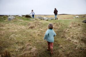 Two children and an adult running along grass