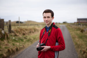 Portrait of Seonaidh on a track holding his camera